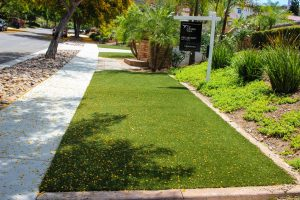 artificial turf on front yard near sidewalk and for sale home sign