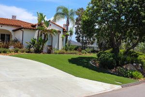 Artificial turf installed at luxury home, front yard near driveway