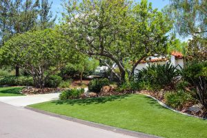 Artificial turf installed at luxury home, front yard with landscaping