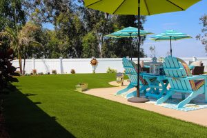 Artificial turf in backyard with patio furniture and umbrellas
