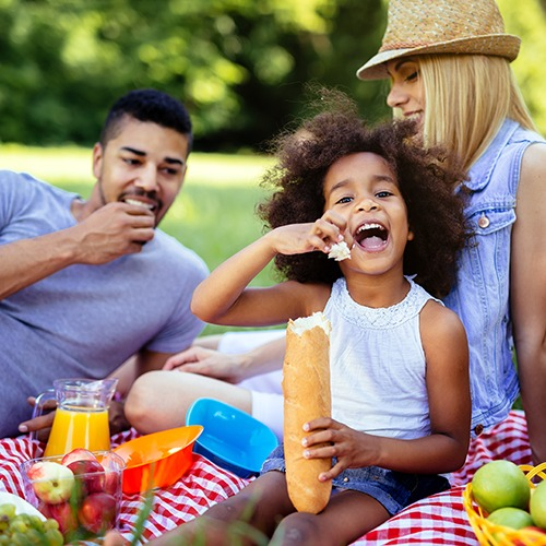 family picnicking on grass outdoors