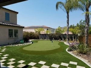 putting green in small backyard with various patches of synthetic lawn