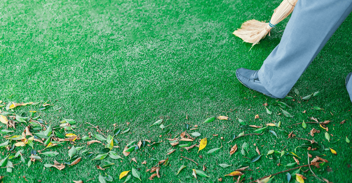 A man sweeping leaves off his artificial lawn, demonstrating how easy the lawn is to maintain.