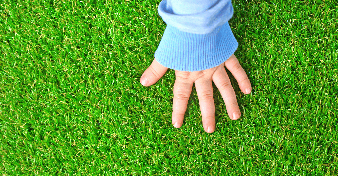 baby hand against grass