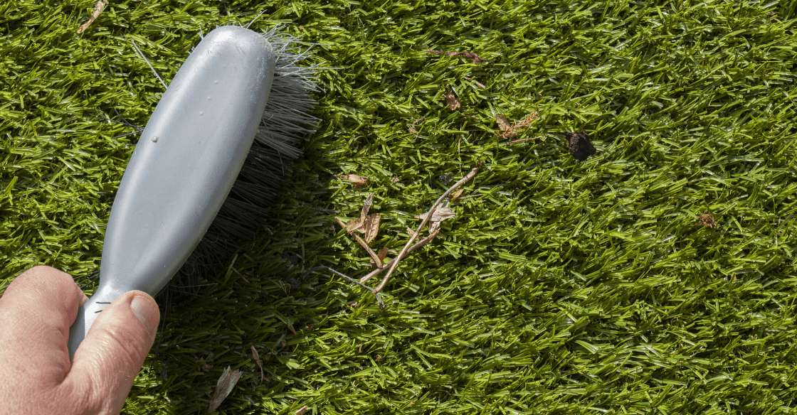 Cleaning artificial turf with brush