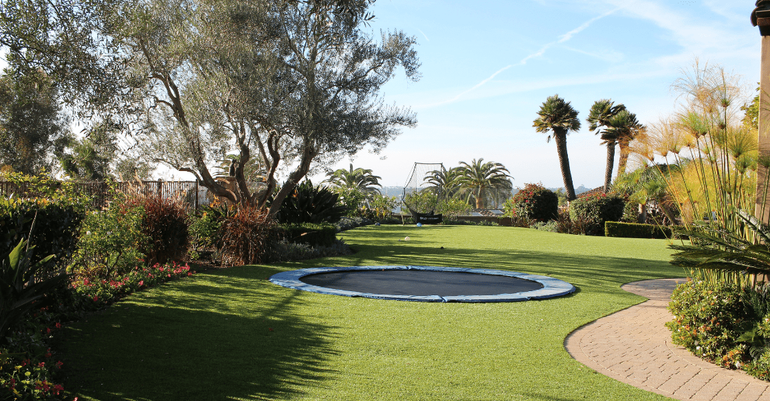 in-ground trampoline surrounded by artificial turf