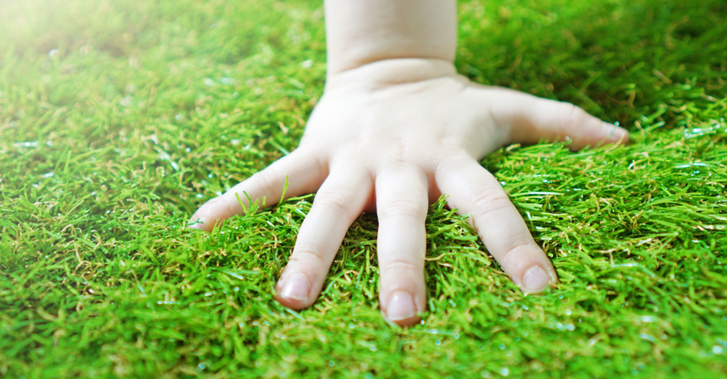 person pressing their hand on their artificial lawn